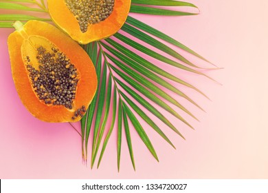 Top view of ripe half cut papaya on color background. Healthy summer food concept with tropical fruits, flat lay