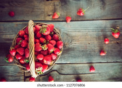 Top view ripe sweet strawberries in wicker basket on wooden rustic table. Agriculture farmer harvest. concept. Eco, organic vegitarian summer diet food. Vintage toning. Selective focus. Copy space