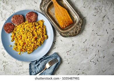 top view of a risotto with vegetables and vegan beet cutlets served on a blue dish on a gray concrete backdrop. also in the frame an old fork on a blue cloth napkin and a wooden kitchen spatula