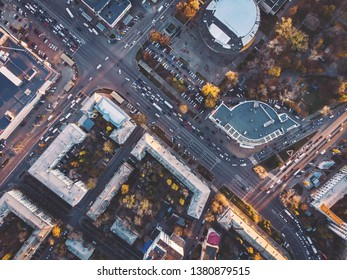 Top view of road intersections and junctions in midtown, car traffic among urban buildings, modern European transportation infrastructure, aerial view from drone, toned