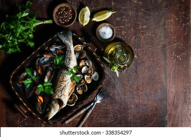 Top view of roasted  seabass and mussels in a dish on vintage wooden table with copy space.