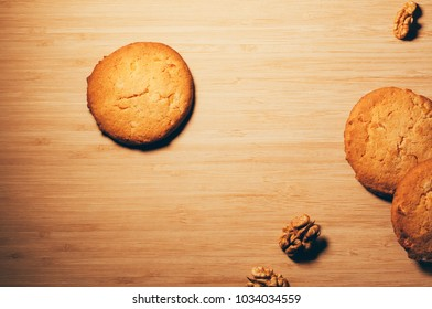 Top view of round crunchy sweet biscuits with candied fruit and nuts, on textured wooden background
