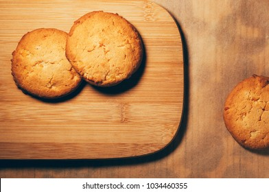 Top view of round crunchy sweet biscuits with candied fruit, on wooden pastry board