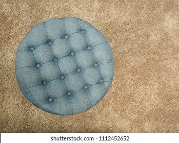 Top view of round fabric blue pouf with buttons and squares. Brown carpet background