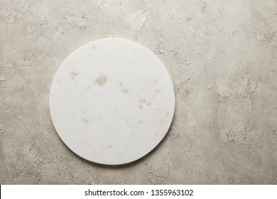 Top view of round marble tray on textured surface