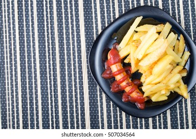 Top view of the Russian national dish - fried sausage with tomato ketchup and a side dish of fried potatoes
