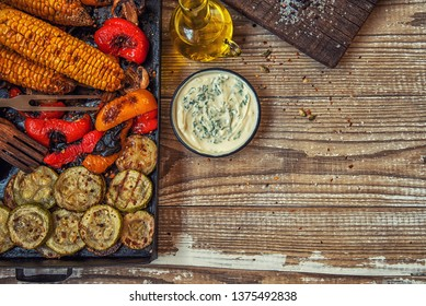 Top view of rustic kitchen table with grilled vegetables on wooden vintage table. Organic vegetables ready to eating.