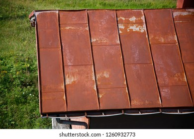 Top view of rusty metal roof. Old rural architecture fragment with extensive copyspace. Original backround with authentic texture on the subject of depressive region, decadence, breakdown, stagnation.