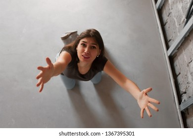 Top view of a sad girl sitting on floor and raise her hands meaning misfortune