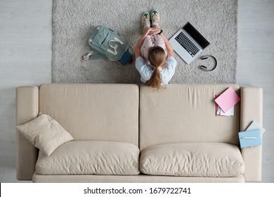 Vue de dessus d'une adolescente triste embrassant ses jambes en s'asseyant sur le sol par un canapé alors qu'elle étudiait à la maison pendant sa quarantaine