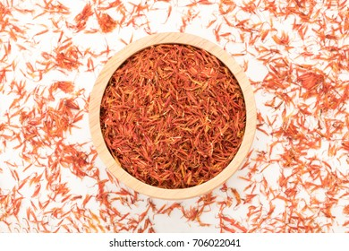 top view of safflower in wooden bowl on white background