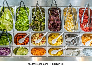 Top view of salad bar with various types of vegetables and fruits including lettuce, tomato, corn, egg, watermelon, carrot, cucumber, and more