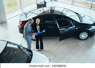top view of sales agent talking with customer in car dealership showroom