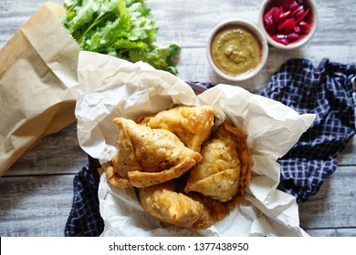 Top view samosas served in wooden bowl with oil absorbing cooking paper on grey paint wood planks background with napkin, mint-cilantro dipping sauce, red onion chutney, fresh coriander in paper bag.