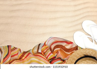 Top view of sandals beach ,Craft hat and multi color scarf on sand beach background.Copy space empty blank for text.Hipster vacation,Summer Day off holiday traval theme concept.