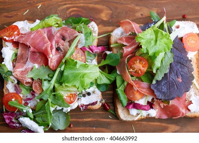Top view at sandwich with prosciutto, tomato, salad and soft cheese on a wooden rustic background
