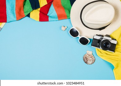 Top view sandy beach concept. Graphical paper background with copy space around products. Punchy pastel colours and frame composition. Hipster or millenial traveler theme.