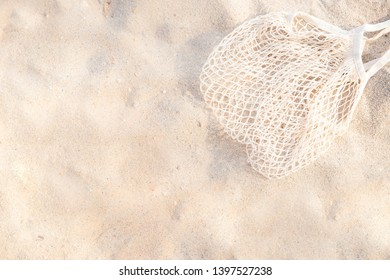 Top view of sandy beach with beach mesh bag Background with copy space. background usage or present your product