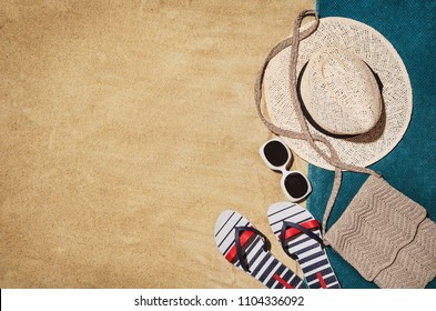 Top view of sandy beach with towel frame and summer accessories. Background with copy space and visible sand texture. Border composition made of towel