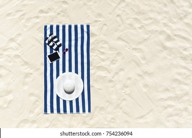 Top view of sandy beach with towel frame and summer accessories. Background with copy space and visible sand texture.