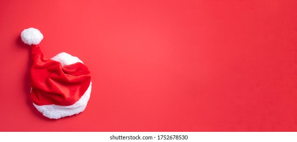 Top view of Santa's hat on red background. Christmas, New year, winter holidays season concept. Banner. Top view. Copy space. Advent time. Festive greeting card. - Shutterstock ID 1752678530