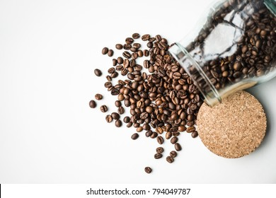 top view of scattered coffee beans from glass bottle and cork isolated on white