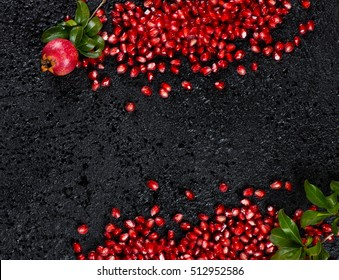 Top view of scattered on a black  background fresh pomegranate seeds and twigs of pomegranate tree with fruit and green leaves with copy space