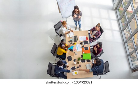 Top view scene of Asian and Multiethnic Business people with casual suit sitting and Fist Bumping Corporate Colleagues Teamwork with happy action in the modern workplace, people business group concept