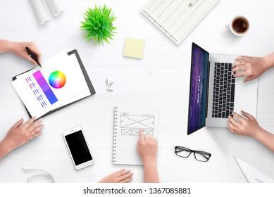 Top view scene of web design team work desk. Laptop computer with flat design web site concept, idea sketch on paper, color palette, cup of coffee, plant, glasses on desk.