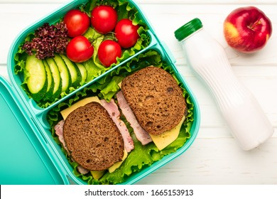 Top view of school lunch box with sandwiches and vegetables and a bottle of yogurt: a concept of healthy and balanced nutrition.