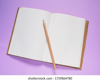 Top view, School notebook on a purple background,  Notebook and pencil on color paper