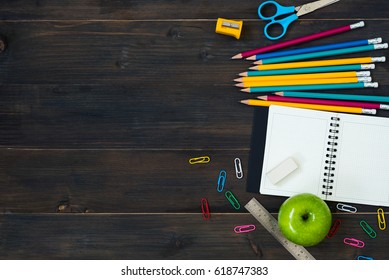 Top view of School Supplies on a wooden table with space for text