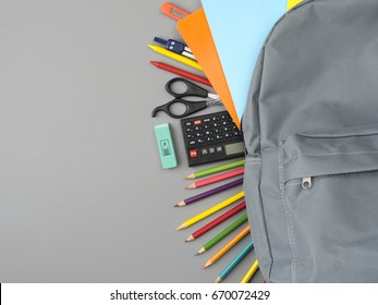 Top view of school supplies on grey background