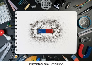 Top view of science equipment, science laboratory accessories, blank paper and bar magnet magnetic field on black background. Science background concept.