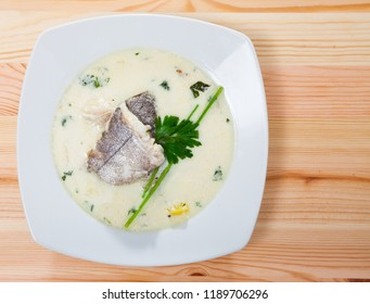 Top view of Scottish soup with smoked haddock, potatoes and onions (Cullen skink) served in white plate with greens on wooden background