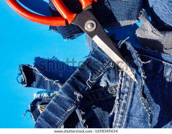 Top view of scraps of old blue jeans and a red industrial scissor on a blue background on a sunny day. Room for copy.
