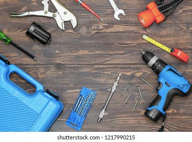 Top view of screwdriver, cordless, electric drill,plier carpenter set with tool on a wooden table.