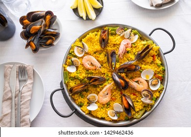 Top view of Seafood Paella with  prawns, clams, mussels on saffron rice and vegetables served in  traditional frying pan on the table.