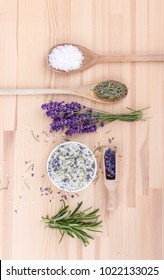 Top view of seasoned salt with rosemary and lavender blossoms  on a wooden backgroun