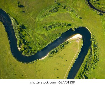 Top view of the Seim River (Ukraine), surrounded by trees and meadows on its banks, view from the top - aerial photo