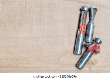 top view of a selection of red woodworking router bits for router machine on a wooden surface