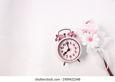Top view selective focus vintage alarm clock  with beautiful bouquet flowers  on white background. Love anniversary, dating and present concept. Abstract background.
