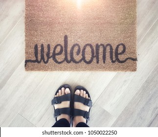 Top view selfie feet with foot scraper welcome word