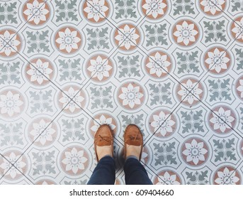 Top view selfie of feet in leather shoes on the vintage seamless floor background with copy space