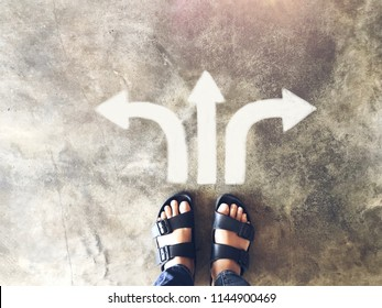 Top view of selfie feet on concrete floor background with white drawn left and right and move forward direction arrows , decision making , Choices concept, where to go, directions, business solutions