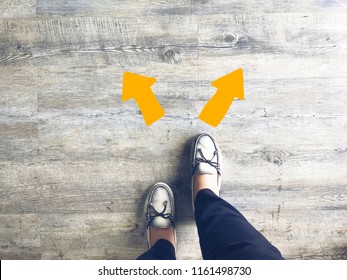 Top view of selfie feet on wooden floor background with yellow drawn left and right direction arrows , decision making , Choices concept, where to go, directions, business solutions