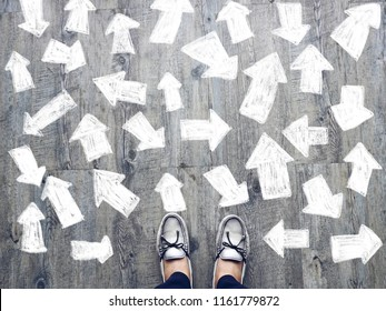 Top view of selfie feet on wooden floor background with white drawn many direction arrows , decision making , Choices concept, where to go, directions, business solutions