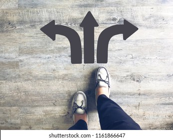 Top view of selfie feet on wooden floor background with gray drawn left, towards and right direction arrows , decision making , Choices concept, where to go, directions, business solutions