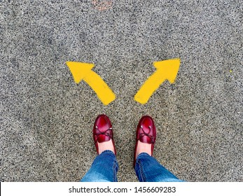 Top view of selfie feet on concrete floor background with yellow drawn left and right direction arrows , decision making , Choices concept, where to go, directions, business solutions,uncertainty