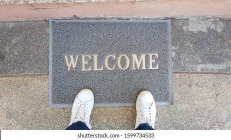 Top view of selfie feet on welcome mat, on wooden floor background , decision making ,